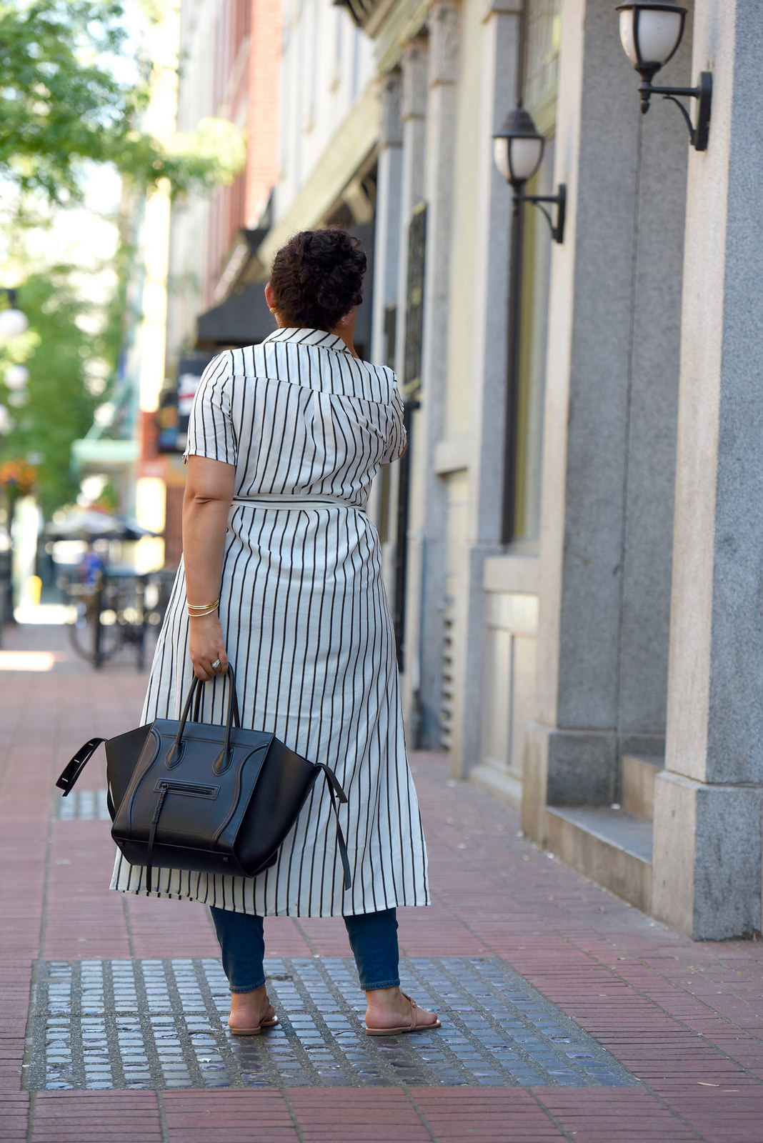 Tanesha Awasthi (formerly known as Girl with Curves) wearing a stripe shirtdress, skiny jeans and Celine Phantom in Gastown, Vancouver.