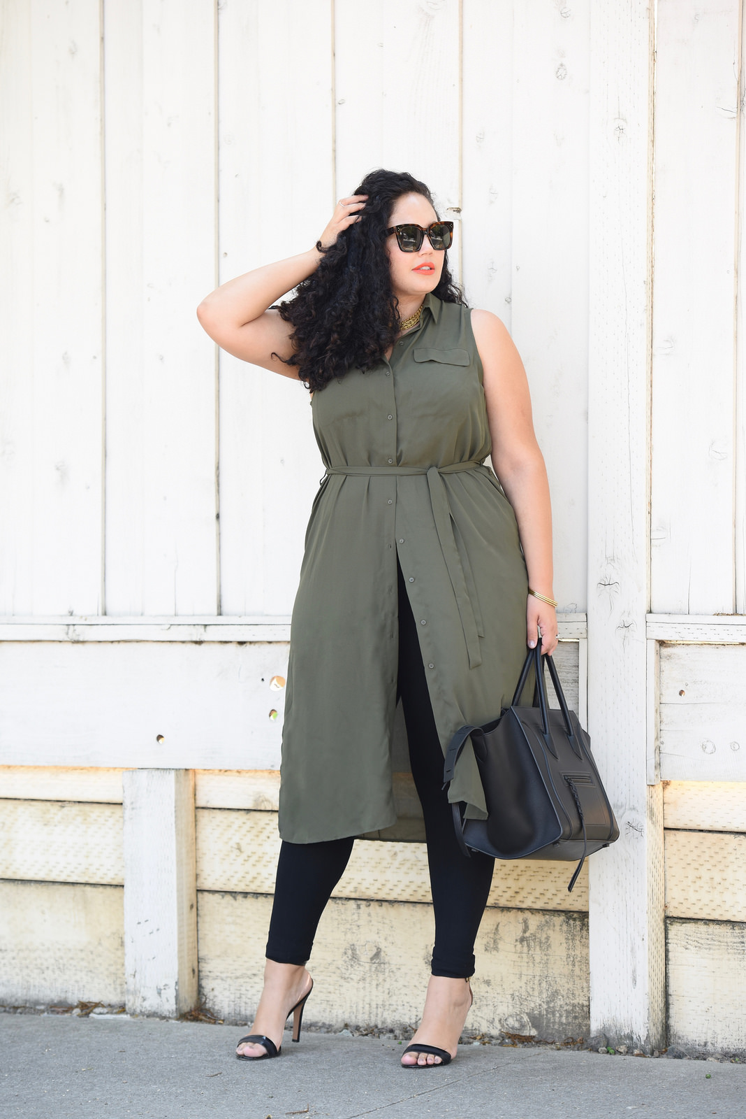 Tanesha Awasthi, also known as Girl With Curves, wearing a plus size shirtdress over leggings, Celine Audrey sunglasses, heels and Celine phantom.