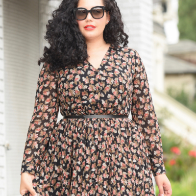 Tanesha Awasthi, also known as Girl with Curves, wearing a long sleeve plus size floral midi dress.