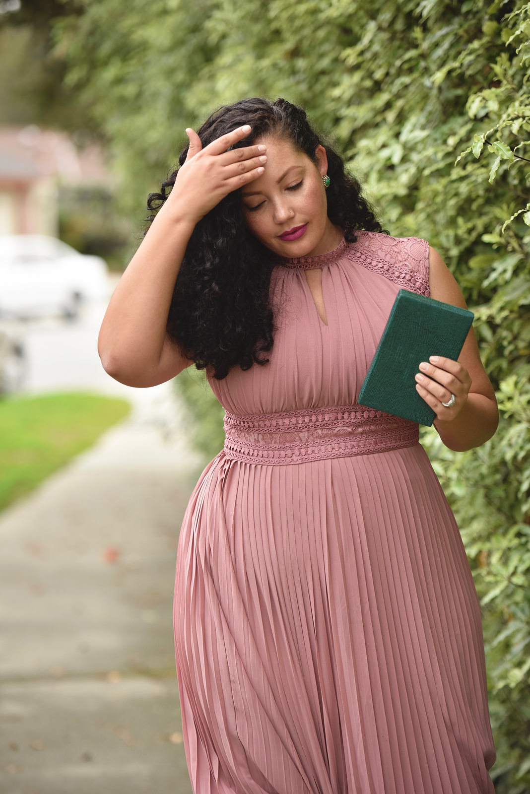 Girl With Curves blogger Tanesha Awasthi wears a lace detail plus size maxi dress and emerald green accessories.