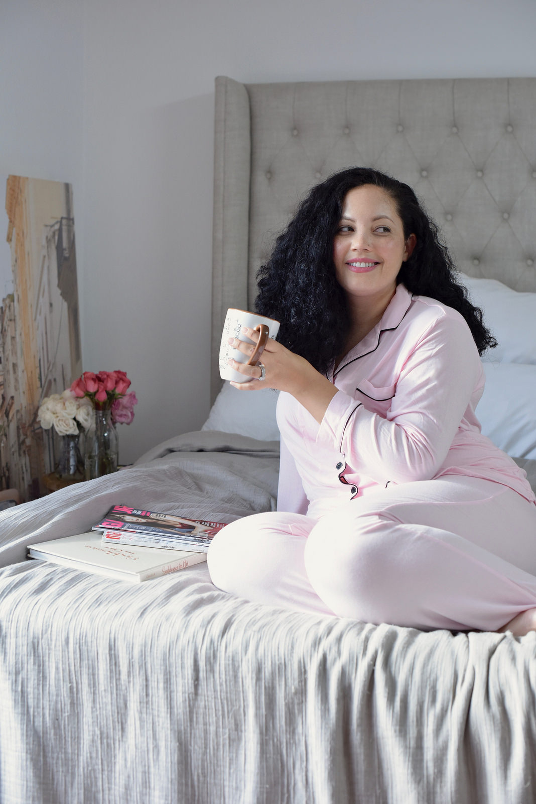 Tanesha Awasthi of Girl With Curves, lounging in Pink and Black pretty pajamas from Nordstrom on a Restoration Hardware bed.